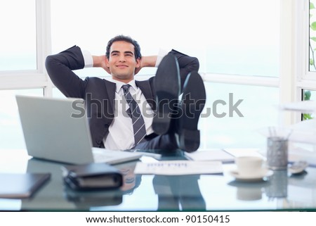 Smiling businessman relaxing in his office - stock photo