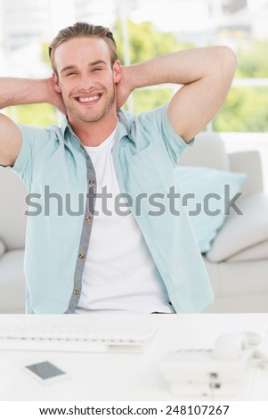 Smiling businessman relaxing with hands behind head in his office - stock photo