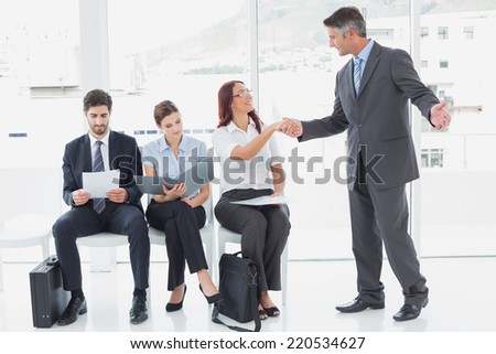 Smiling businessman shaking co-workers hand at work - stock photo