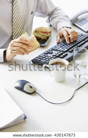 Smiling businessman sitting at office desk and having a lunch break - stock photo