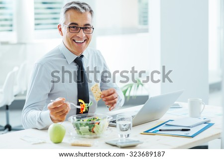 Smiling businessman sitting at office desk and having a lunch break, he is eating a salad bowl - stock photo