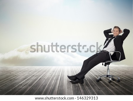 Smiling businessman sitting in a swivel chair on wooden boards with heavenly backdrop - stock photo