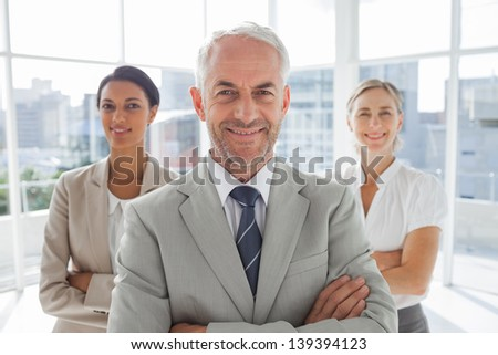 Smiling businessman standing in front of colleagues with arms folded - stock photo