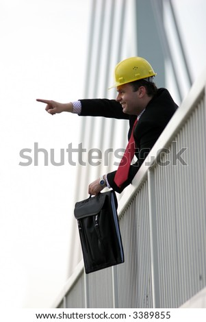 Smiling businessman standing on bridge and pointing - stock photo