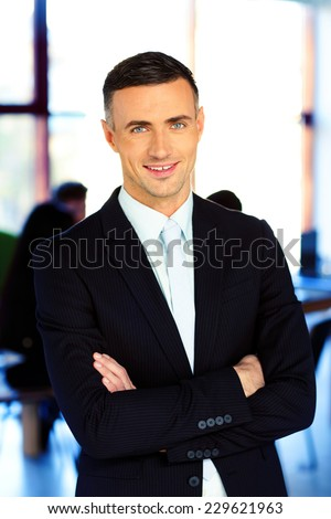 Smiling businessman standing with arms folded in front of colleagues - stock photo