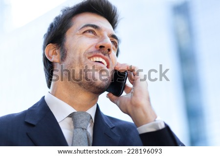 Smiling businessman talking at the phone - stock photo
