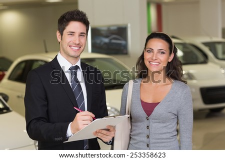 Smiling businessman undersign a car contract at new car showroom - stock photo