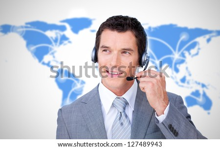 Smiling businessman using headset on world map background - stock photo