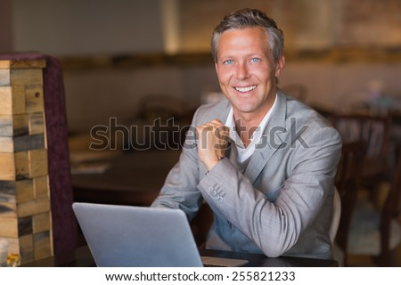 Smiling businessman using his laptop at the cafe - stock photo