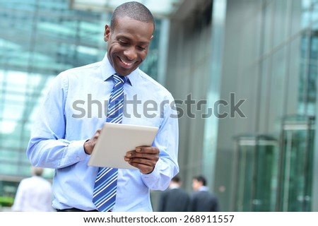 Smiling businessman using his new digital tablet - stock photo