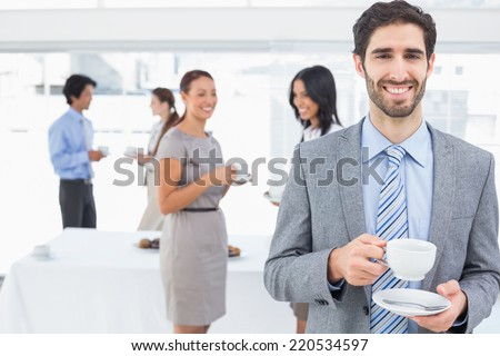 Smiling businessman with a drink at work - stock photo