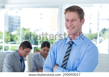 Smiling businessman with arms crossed at office - stock photo