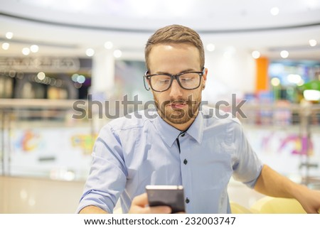 Smiling Businessman with electronic device on hand, blurred background of indoor shopping mall - stock photo