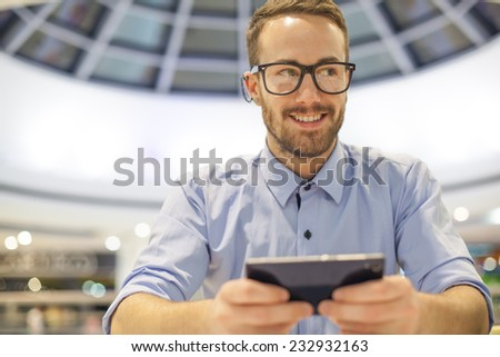 Smiling Businessman with electronic device on hand, blurred background of indor shopping mall - stock photo
