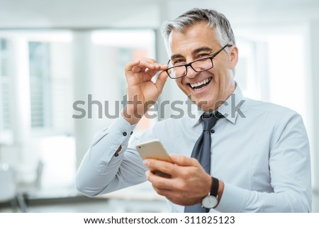 Smiling businessman with eyesight problems, he is adjusting his glasses and reading something on his mobile phone - stock photo