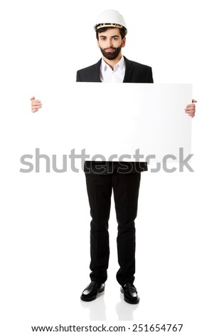 Smiling businessman with hard hat holding empty banner. - stock photo