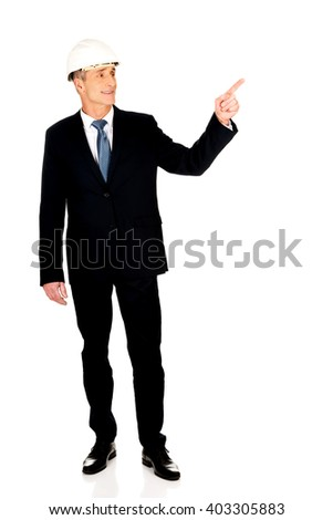 Smiling businessman with hard hat pointing up - stock photo