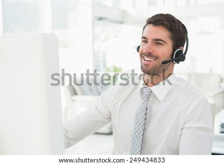 Smiling businessman with headset interacting in his office - stock photo