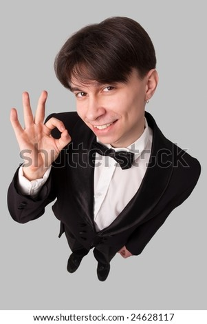 smiling businessman with O.K. on a grey background - stock photo