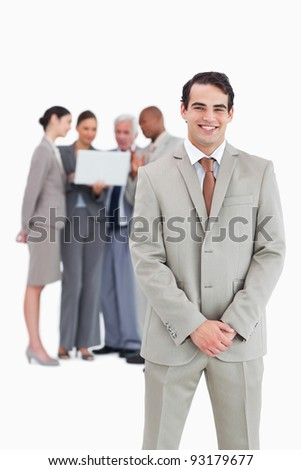 Smiling businessman with team behind him against a white background - stock photo