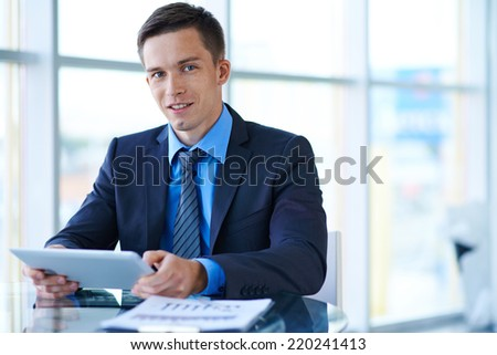 Smiling businessman with touchpad sitting at workplace in office - stock photo