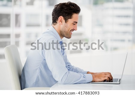 Smiling businessman working on computer in office - stock photo