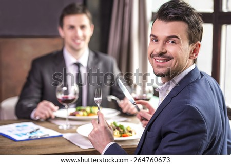 Smiling businessmen eating during a business lunch. Business meeting. - stock photo