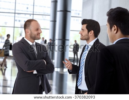 Smiling businessmen in formal suit meeting and talking inside office building. - stock photo