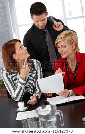 Smiling businesspeople at discussion of documents at meeting. - stock photo