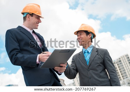 Smiling businesspeople in hardhats discussing a contract - stock photo