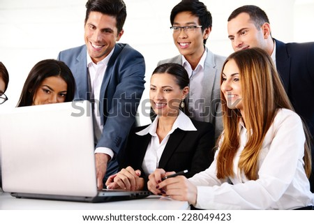 Smiling businesspeople working on the laptop together - stock photo