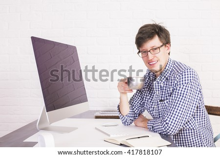 Smiling businessperson in office drinking coffee from iron mug at desk with huge computer screen. White brick background. Mock up - stock photo