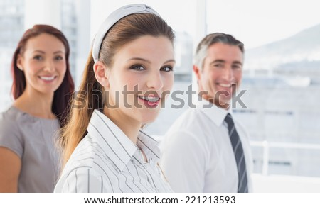 Smiling businesswoman and her colleagues in the office - stock photo