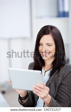 Smiling businesswoman browsing using her tablet inside the office - stock photo