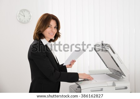 Smiling Businesswoman Copying Paper On Photocopy Machine In Office - stock photo
