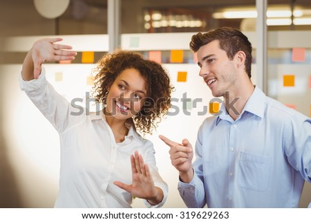 Smiling businesswoman discussing with male colleague in office - stock photo