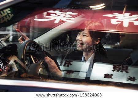 Smiling businesswoman driving through the city and pointing - stock photo