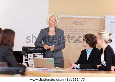 Smiling businesswoman giving a presentation to a group of business men and women seated at a table - stock photo