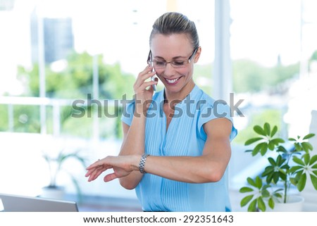 Smiling businesswoman having a phone call and checking time in an office - stock photo