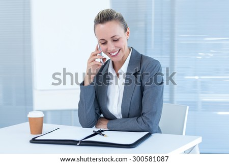 Smiling businesswoman having phone call in the office - stock photo