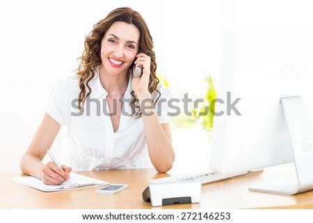 Smiling businesswoman having phone call on white background - stock photo