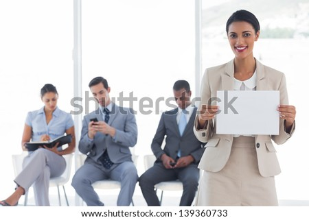 Smiling businesswoman holding a blank notice in front of waiting business people - stock photo