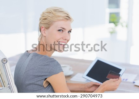 Smiling businesswoman holding credit card and tablet in her office - stock photo