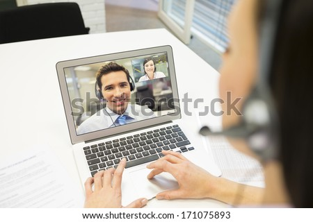 Smiling Businesswoman in the office on video conference, headset, Skype - stock photo