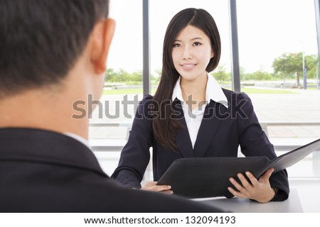 smiling businesswoman interviewing with businessman in office - stock photo