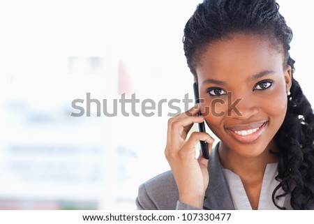Smiling businesswoman looking ahead while talking on a phone - stock photo