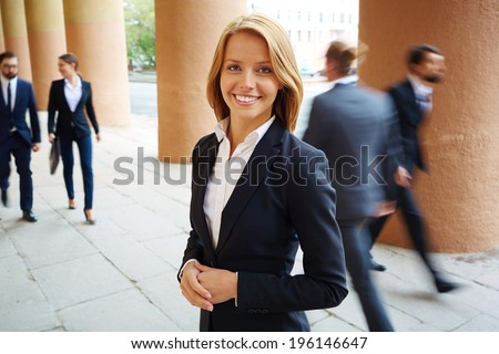 Smiling businesswoman looking at camera with walking people on background - stock photo