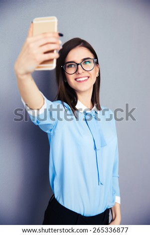 Smiling businesswoman making selfie photo on smartphone. Wearing in blue shirt and glasses. Standing over gray background - stock photo