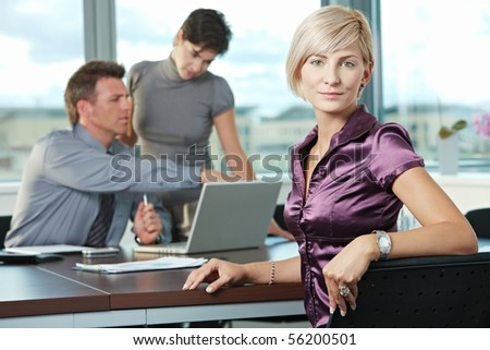 Smiling businesswoman on business meeting at office with team in background. - stock photo