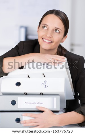 Smiling businesswoman or office working with a stack of files in her arms showing a positive enthusiastic approach to working under pressure - stock photo